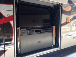 """Custom built entertainment bay loaded with a 40"""" HD Smart TV, HD DVR, Apple TV, sound bar, pull-out refrigerator/freezer and more!"""