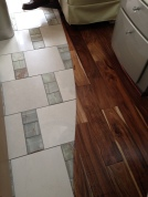 Beautiful hand-scraped wood meets tile in salon hallway.
