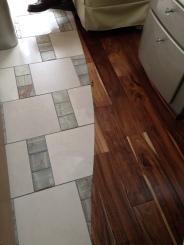 Beautiful hand-scraped wood meets tile in salon hallway.